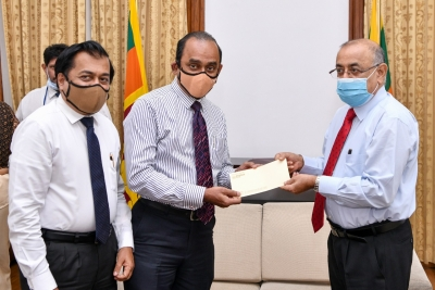 Chairman of People's Bank - Sujeewa Rajapaksa handing over a cheque for Rs. 10 million for the COVID-19 Healthcare and Social Security Fund to the President's Secretary -        Dr. P. B. Jayasundera. Acting Chief Executive Officer/ General Manager - Boniface Silva is also present in the picture
