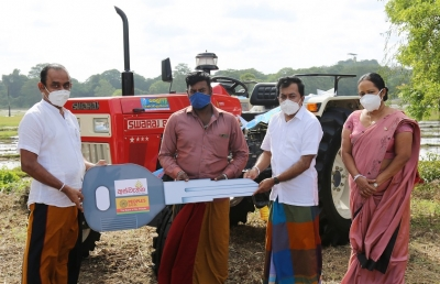 People's Bank Chairman Sujeewa Rajapakse  giving away a loan grant under the Aswenna loan scheme to purchase a tractor. Acting CEO/General Manager Bonniface Silva  Anuradhapura Regional Manager Chandrika Nissanka also in the capture.